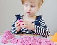 Маленькая кавказская девушка играя с розовым кинетическим песком дома Стоковое Изображение RF