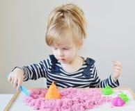 Маленькая кавказская девушка играя с розовым кинетическим песком дома Стоковые Изображения RF