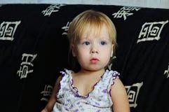 Маленькая красивая девушка смотря ТВ дома стоковое фото