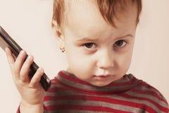 Маленькая красивая девушка с ее умным телефоном Стоковая Фотография