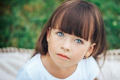 Маленькая красивая милая девушка смотря голубые глазы камеры Стоковое Изображение RF
