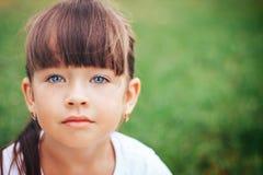 Маленькая красивая милая девушка смотря голубые глазы камеры Стоковые Изображения RF