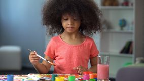Маленькая курчавая африканская девушка крася изображение и усмехаясь, счастливое детство стоковые фотографии rf