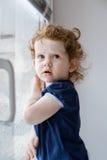 Маленькая курчавая девушка в окне стоковое изображение rf