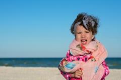 Маленькая курчавая девушка кричащая и быть капризный на пляже моря стоковое фото