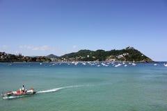 Маленькая лодка возглавленная к порту городка стоковая фотография