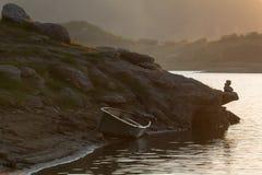 Маленькая лодка вытягивана вверх на береге озера ждать другой день рыбной ловли Стоковые Изображения RF