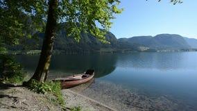 Маленькая лодка в идилличной высокогорной долине с озером в раннем лете HD1080p, Bohinj, Словения сток-видео