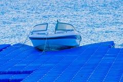 Маленькая лодка состыкованная на голубой пристани Стоковые Изображения