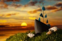 Маленькая лодка с раковинами на мхе на заходе солнца Стоковая Фотография