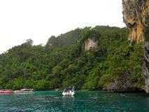 Маленькая лодка с туристами остановленными около огромного утеса так как туристы смогли понять океан и увидеть подводный мир стоковое изображение rf