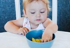 Маленькая милая белокурая голубоглазая девушка есть макаронные изделия с руками стоковая фотография rf