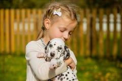 Маленькая милая белокурая девушка играя с ее далматинским outdoo щенка, на солнечный теплый день осени забота концепции любимчико стоковое фото