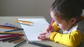 Маленькая милая маленькая девочка рисует ее дом с покрашенными карандашами 4K акции видеоматериалы