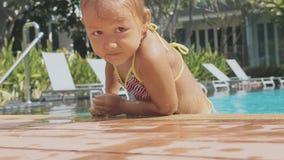 Маленькая милая девушка взбирается из бассейна, в замедленном движении сток-видео