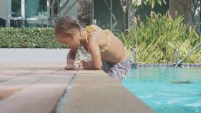 Маленькая милая девушка взбирается из бассейна, в замедленном движении акции видеоматериалы