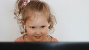 Маленькая милая девушка в наушниках смотрит компьютер монитора экрана Смешной ребенок смотря ТВ, видео, шарж или играть акции видеоматериалы