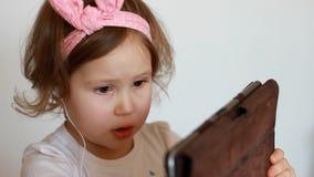 Маленькая милая девушка в наушниках смотрит ПК таблетки монитора экрана Смешной ребенок смотря ТВ, видео, шарж или играть сток-видео