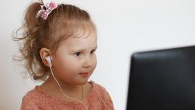 Маленькая милая девушка в улыбках наушников смотрит компьютер монитора экрана Смешной ребенок смотря ТВ, видео, шарж или сток-видео