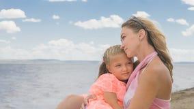 Маленькая милая девушка и молодая мать на пляже Стоковое фото RF