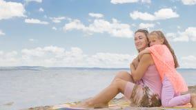 Маленькая милая девушка и молодая мать на пляже Стоковые Фото