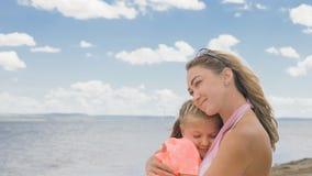 Маленькая милая девушка и молодая мать на пляже Стоковые Фотографии RF