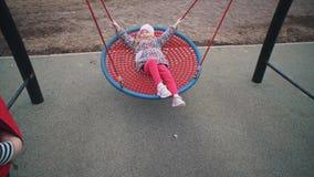 Маленькая милая девушка отбрасывая на сильном чистом круглом качании сток-видео