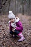 Маленькая милая девушка сидит на пути в лесе осени Стоковые Изображения