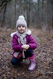 Маленькая милая девушка сидит на пути в лесе осени Стоковые Фотографии RF