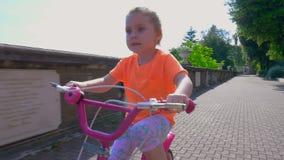 Маленькая милая девушка учит ехать на велосипеде акции видеоматериалы