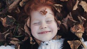 Маленькая милая девушка redhead лежит на желтые листья в парке осени Она смотря intot камера и усмехаться Листья