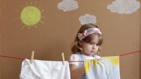 Маленькая милая рука девушки кладя зажимку для белья и висит вне для того чтобы высушить одежды Схематическое домашнее хозяйство  сток-видео