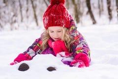 Маленькая милая хоронить девушки в снеге Стоковые Изображения