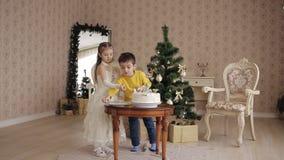 Маленькая сестра и брат украшают торт рождества красивые дети в просторном и светлая комната около рождества акции видеоматериалы