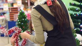 Маленькая смешная девушка в играх и танцах супермаркета с гирляндами акции видеоматериалы