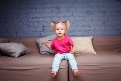 Маленькая смешная девушка изнеживая и играя на софе дома показывая нагие пятки Он смеется над показывающ его язык и зубы Она Д-р стоковая фотография