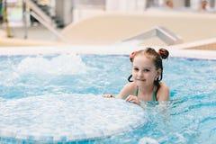 Маленькая счастливая девушка играя в джакузи стоковое изображение rf