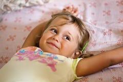 Маленькая усмехаясь девушка лежа на кровати стоковое фото