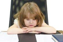 Маленькая уставшая девушка сидя на взрослом рабочем месте в офисе стоковое изображение