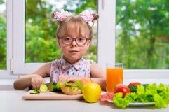 Маленькая школьница подготавливает обед, здоровую еду стоковые фото