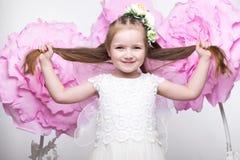 Маленькая fairy девушка в белом платье на предпосылке цветков Стоковое фото RF