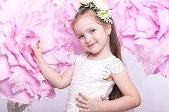 Маленькая fairy девушка в белом платье на предпосылке цветков Стоковые Изображения RF
