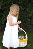 Маленькие белокурые пасхальные яйца удерживания девушки в корзине стоковые фотографии rf