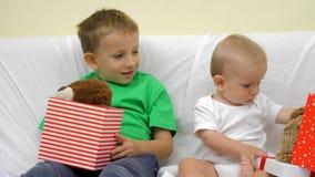 Маленькие братья смотря в присутствующих коробках, младенце и ребенке находят плюшевый медвежонок в коробке сток-видео