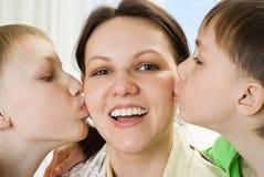 Маленькие братья целуя его маму Стоковые Изображения
