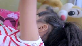 Маленькие девочки азиатских детей используя умный телефон дома акции видеоматериалы