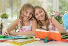 Маленькие девочки делая домашнюю работу Стоковое Изображение