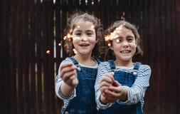 Маленькие девочки держа бенгальские огни outdoors стоковые фотографии rf
