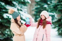 Маленькие девочки держа свет горящей свечи рождества outdoors на красивый день снега зимы и греют их руки Стоковые Фотографии RF