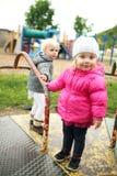 Маленькие девочки играя на винтажном Весел-идти-круглом снаружи на Стоковое фото RF